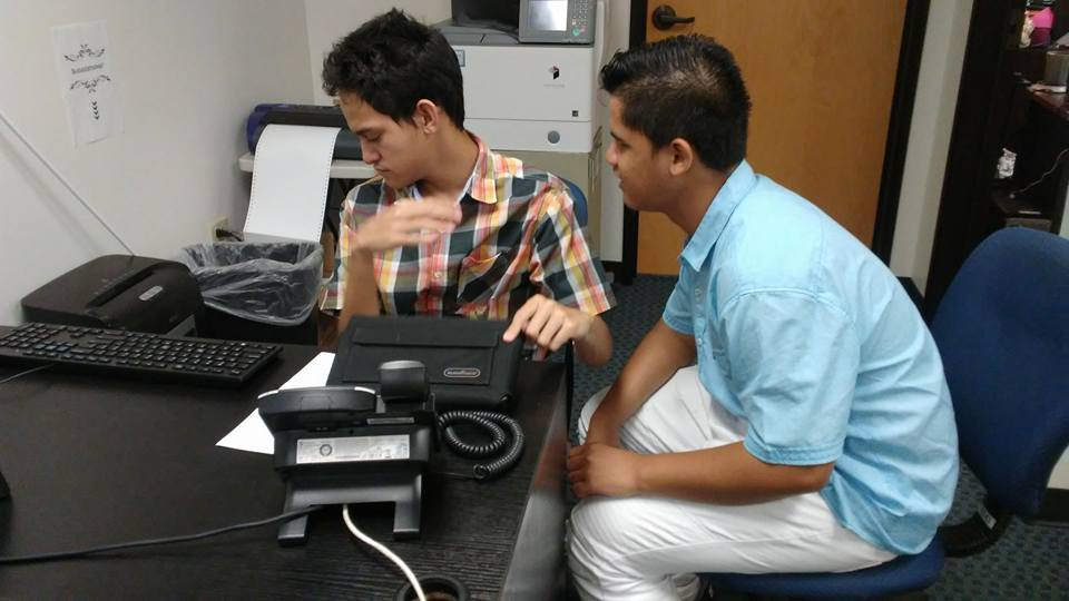 two youth using braille equipment