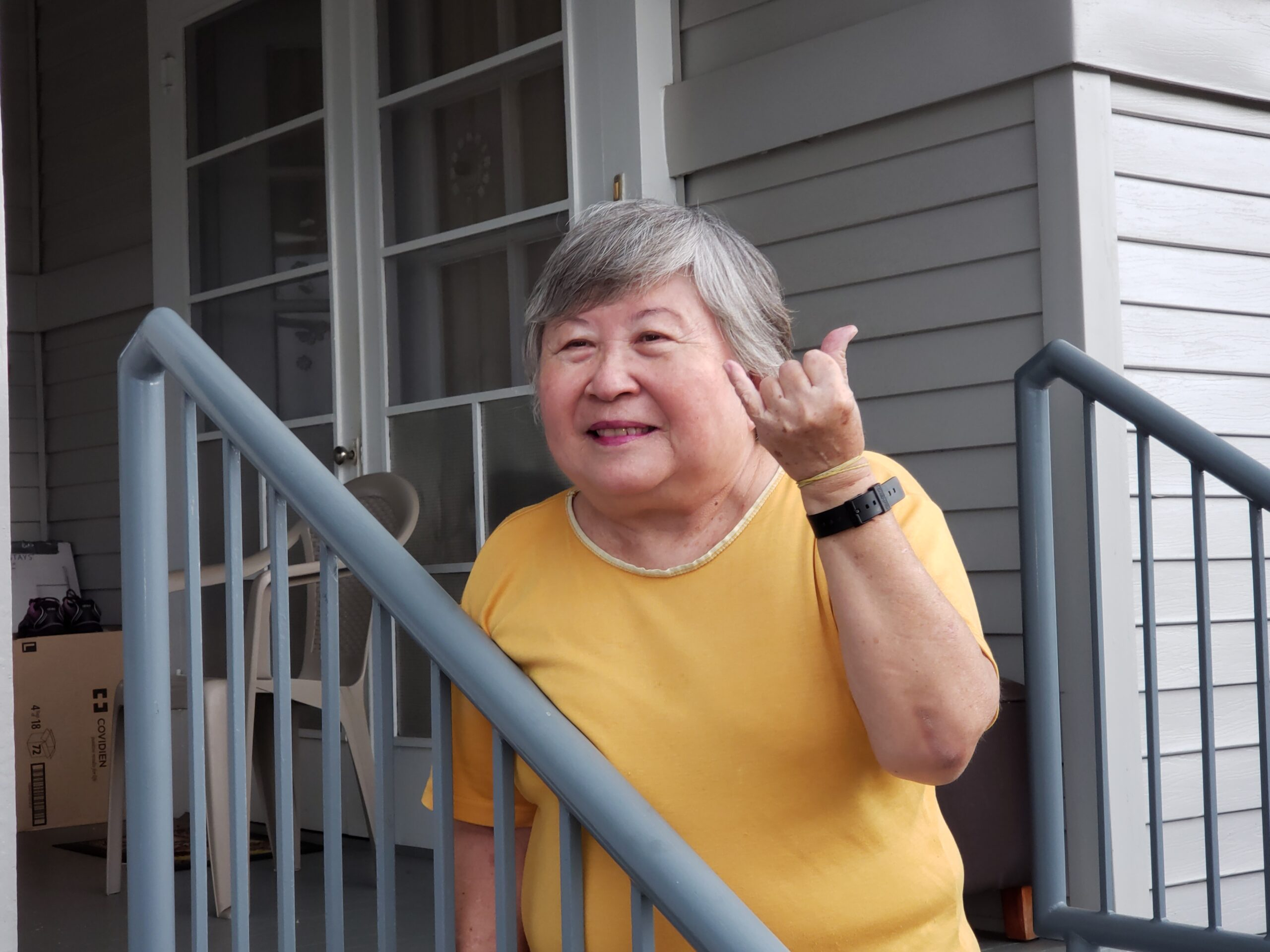 A senior client stands on a porch and is holding up a shaka.