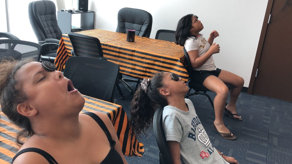 Youth girls sit on chairs with their heads leaned back. Each girl has an oreo cookie placed on their forheads and they are making funny facial expressions to get the cookie into their mouths without using their hands.
