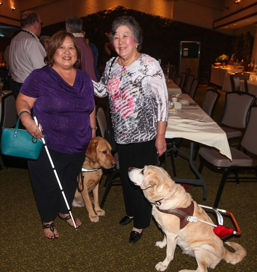 Two women stand and smile for a photo while their guide dogs lock eyes.