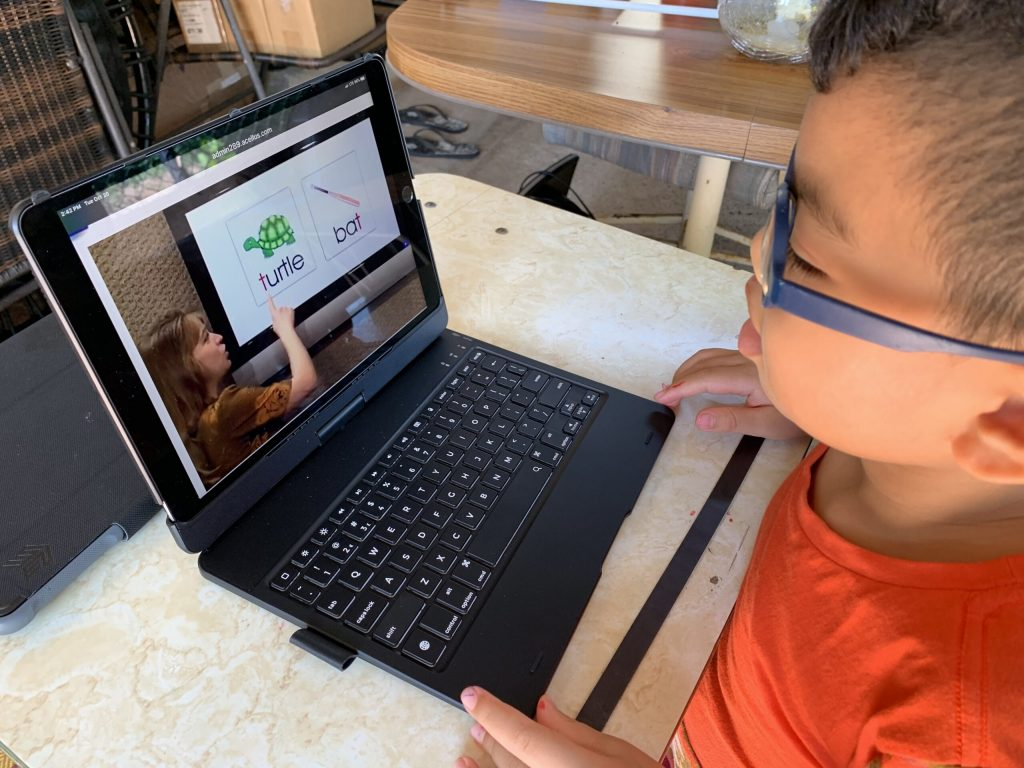 A young boy with glasses uses his iPad to watch an educational video.