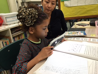 A young girl sits at a classroom table with her teacher. The young girl holds an electronic video magnifier up to a textbook.
